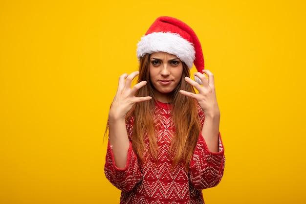 Giovane donna che indossa cappello santa arrabbiato e sconvolto