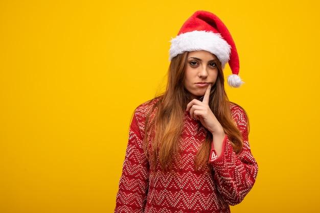 Giovane donna che indossa cappello santa dubitando e confuso