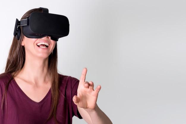 Cuffia avricolare d'uso degli occhiali di protezione di realtà virtuale della giovane donna, scatola del vr. connessione, tecnologia, nuova generazione, concetto di progresso. ragazza che prova a toccare gli oggetti nella realtà virtuale. studio girato su grigio