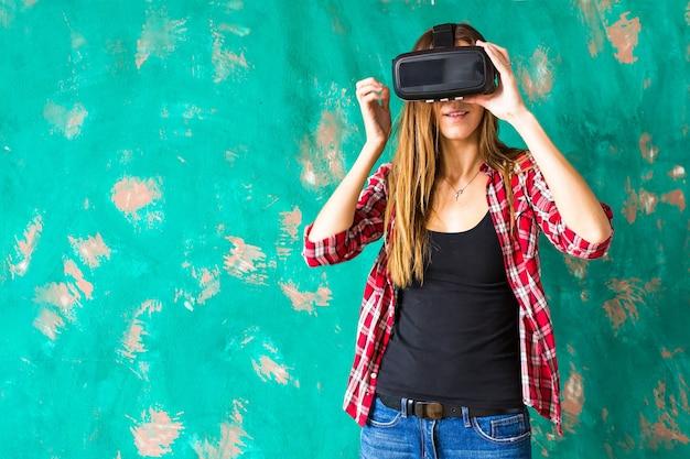 Giovane donna che indossa le cuffie da realtà virtuale in studio.