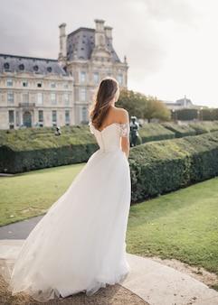 Giovane donna in abito da sposa vicino al castello