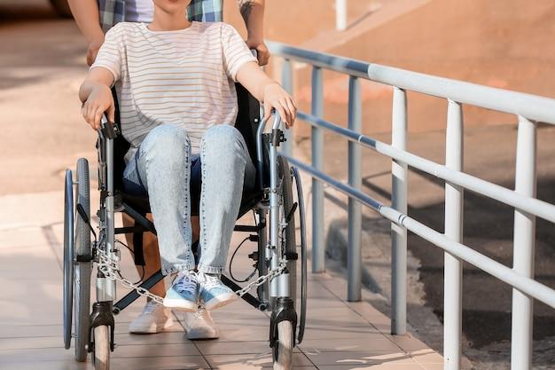 Giovane donna in sedia a rotelle e suo marito sulla rampa all'aperto