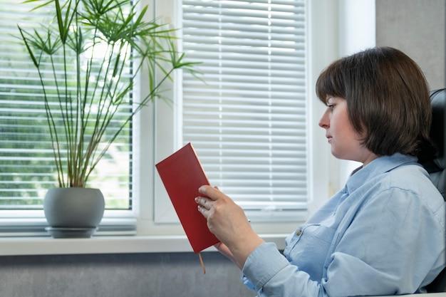 La giovane donna mentre legge il libro è seduta accanto alla finestra. ritratto di donna in poltrona in pelle con libro in mano.