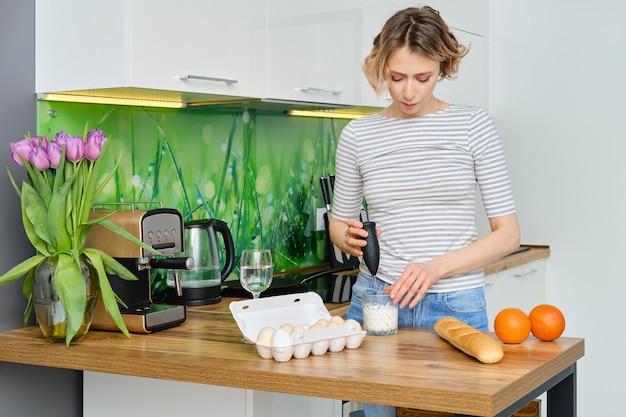 Giovane donna che monta il latte caldo in vetro per cappuccino