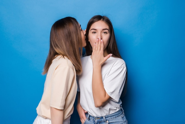 La giovane donna sussurra al suo compagno cattive notizie isolate sulla parete blu