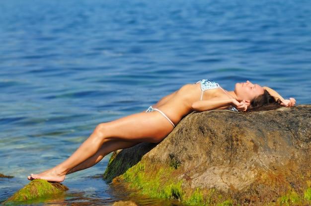Giovane donna in costume da bagno bianco e blu in posa con gli occhi chiusi
