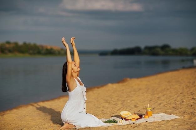 Giovane donna in abito bianco seduto sulla spiaggia di sabbia con le mani in alto e godersi il picnic estivo.