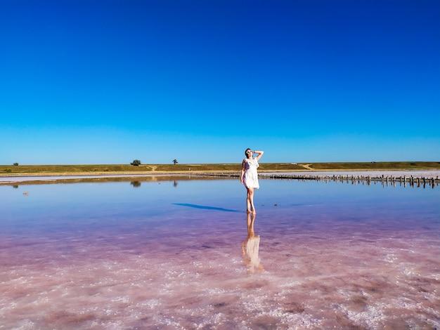 Una giovane donna in abito bianco in piedi nel lago salato rosa in una soleggiata giornata estiva