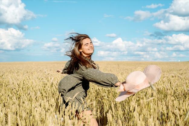 Giovane donna in abito bianco, cappello di paglia, campo di fiori, orecchie di pane. bella ragazza che gode di un campo di fiori, relax all'aperto, concetto di libertà di armonia.