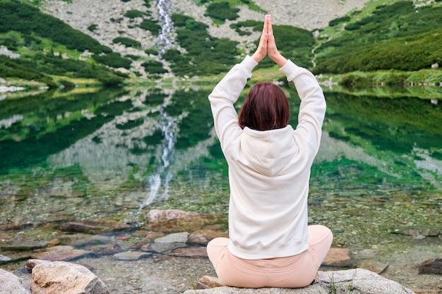 Giovane donna in una felpa con cappuccio bianca a praticare yoga su una riva del lago con acqua trasparente con una splendida vista sulla cascata. meditazione e ricreazione nella natura tra le montagne