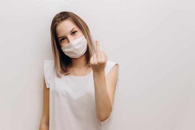 La giovane donna in una mascherina medica bianca mostra il dito medio. donna in una camicetta bianca su sfondo grigio.