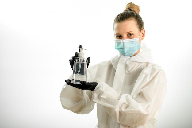 La giovane donna in abiti protettivi bianchi tiene in mano una bottiglia trasparente con un disinfettante