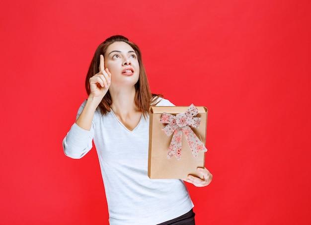 Giovane donna in camicia bianca che tiene una scatola regalo di cartone e indica qualcuno intorno