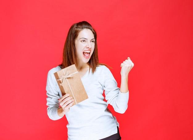 Giovane donna in camicia bianca che tiene in mano una scatola regalo di cartone e mostra un segno positivo con la mano