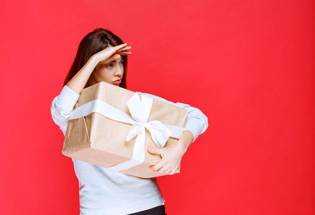 Giovane donna in camicia bianca con in mano una scatola regalo di cartone