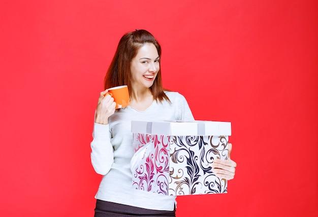 Giovane donna in camicia bianca che tiene una scatola regalo stampata e beve una tazza di bevanda