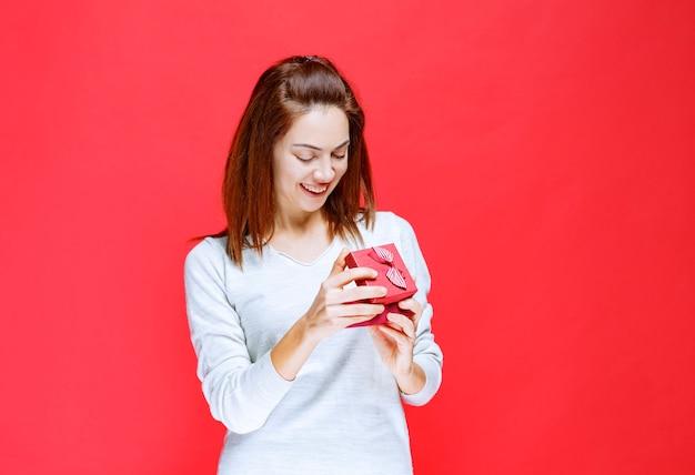 Giovane donna in camicia bianca che tiene in mano una piccola scatola regalo rossa, la apre e si stupisce