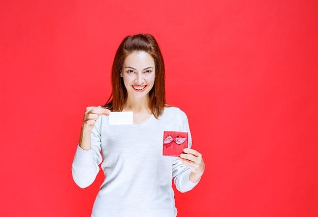 Giovane donna in camicia bianca che tiene in mano una piccola scatola regalo rossa e presenta il suo biglietto da visita