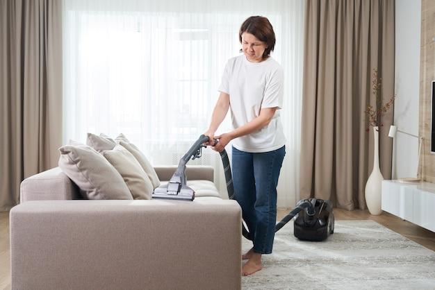 Giovane donna in camicia bianca e jeans pulizia tappeto sotto il divano con aspirapolvere in soggiorno, copia dello spazio. concetto di lavori domestici, pulizie e faccende