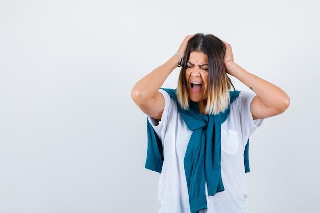 Giovane donna in maglietta bianca che tiene la testa con le mani mentre grida e sembra risentita, vista frontale.
