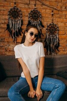 Giovane donna in maglietta bianca in posa in studio su sfondo muro di mattoni