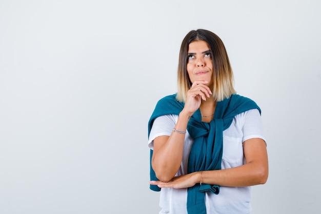 Giovane donna in t-shirt bianca con la mano sul mento e dall'aspetto sognante, vista frontale.