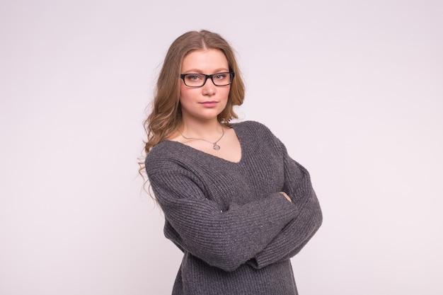 Giovane donna su un muro bianco in un maglione di lavoro a maglia grigio che abbraccia