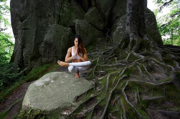 Giovane donna in abbigliamento bianco allenamento facendo yoga nella foresta in equilibrio su una pietra