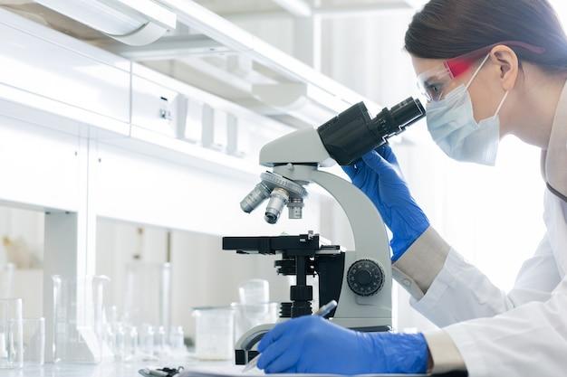 Giovane donna in camice bianco, guanti, occhiali e maschera chinandosi sul microscopio mentre studia le caratteristiche del coronavirus in laboratorio