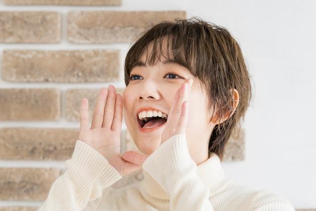 Una giovane donna che si mette una mano sulla bocca e applaude ad alta voce