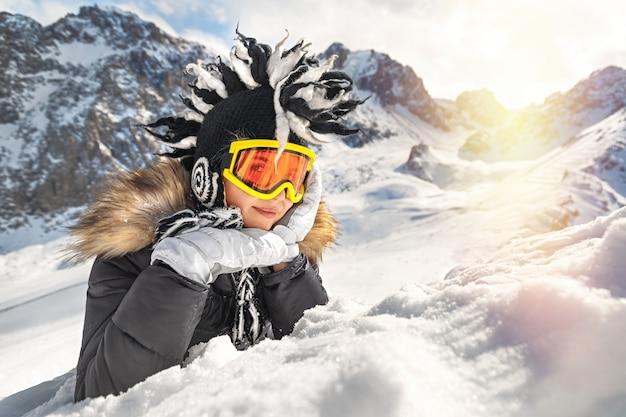 Giovane donna in abiti invernali occhiali e cappello invernale divertente vacanza sulla neve in cima alla montagna