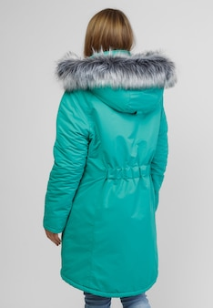 Giovane donna in abiti invernali su sfondo bianco. concetto fotografico per la pubblicità di un piumino.