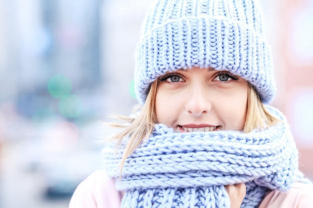 Giovane donna in inverno con cappello e sciarpa a maglia
