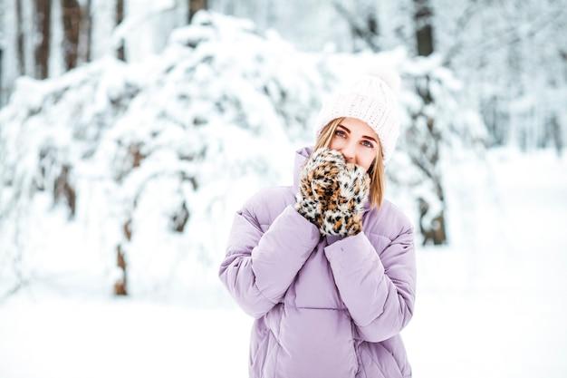 Giovane donna in inverno con sciarpa e cappello lavorato a maglia