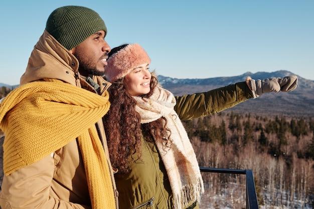 Giovane donna in abbigliamento invernale che mostra le visite turistiche alla sua amica africana