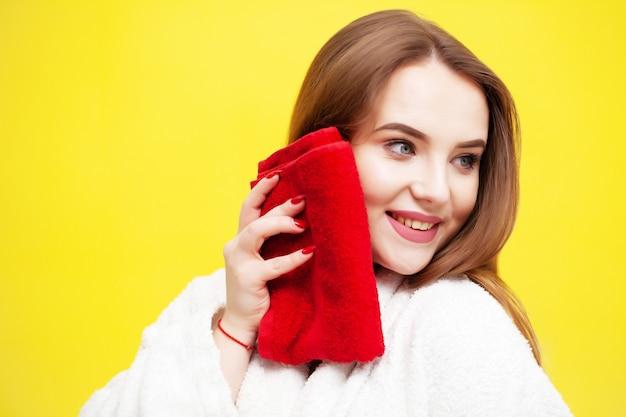 La giovane donna si asciuga il viso con un asciugamano morbido dopo i trattamenti termali.