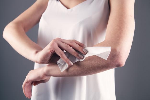 La giovane donna si asciuga la mano con un tovagliolo