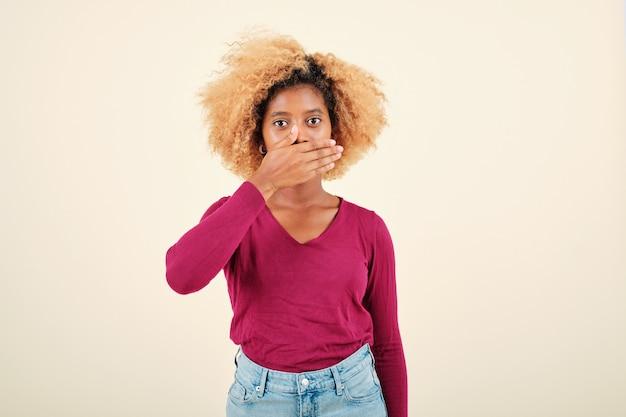 Giovane donna con acconciatura afro che sembra scioccata mentre copre la bocca con le mani su uno sfondo isolato.