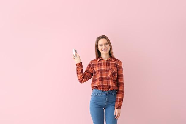 Giovane donna con telecomando del condizionatore d'aria