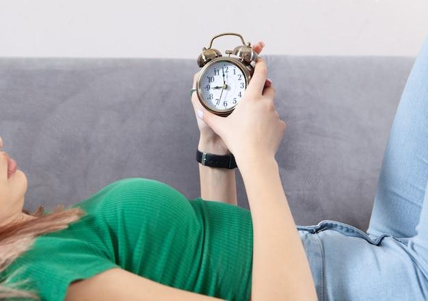Giovane donna con sveglia a casa.