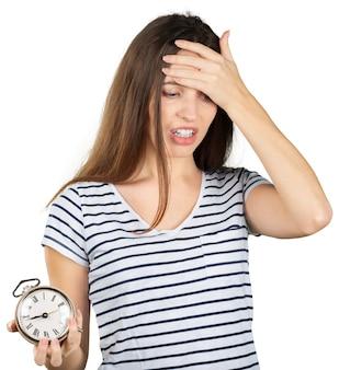Giovane donna con la sveglia isolata su bianco.
