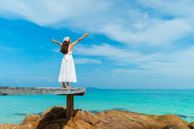 Giovane donna con il braccio sollevato sul ponte di legno e la spiaggia del mare a koh munnork island, rayong, thailandia