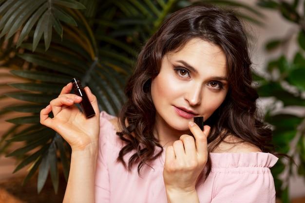 Giovane donna con olio aromatico in mano. goditi il profumo della natura. bella bruna in un maglione rosa.