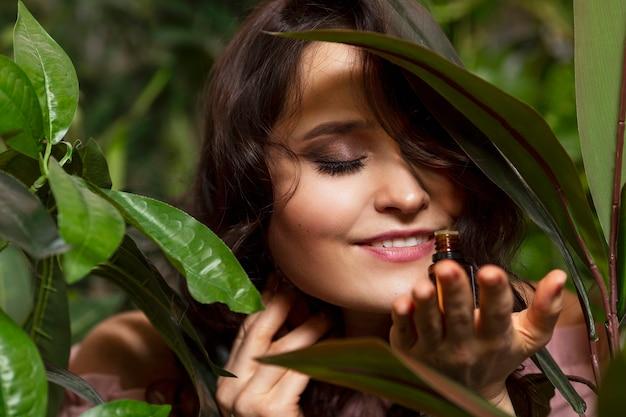 Giovane donna con olio aromatico in mano. goditi il profumo della natura. sorridente bella bruna. avvicinamento.