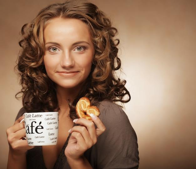 Giovane donna con un caffè aromatico nelle mani