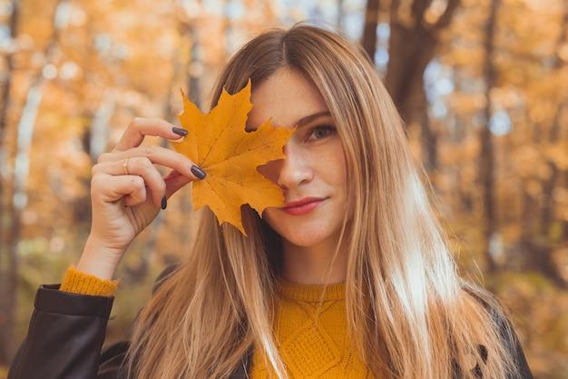 Giovane donna con foglia d'acero arancione autunno su sfondo stagione autunnale.