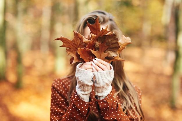 Giovane donna con foglie autunnali