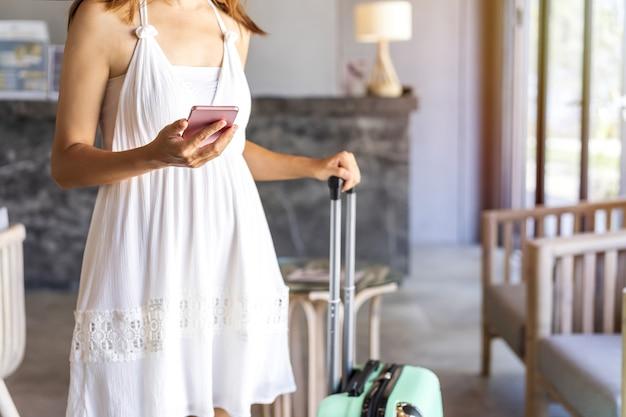 Giovane donna con bagaglio utilizza lo smartphone in attesa di effettuare il check-in nel resort tropicale