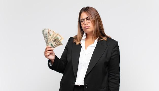 Giovane donna con banconote che si sente triste, sconvolta o arrabbiata e guarda di lato con un atteggiamento negativo, accigliata in disaccordo