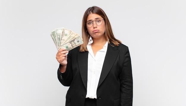 Giovane donna con banconote che si sente triste e piagnucolona con uno sguardo infelice, piange con un atteggiamento negativo e frustrato